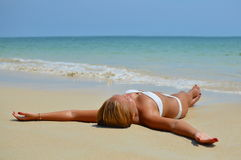 Happy beautiful blond girl lying on the beach Stock Photos
