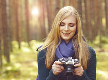 Happy, beautiful blond girl taking pictures in forest. Camp, tou. Rism, hiking concept Royalty Free Stock Images