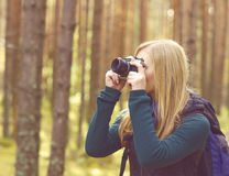 Happy, beautiful blond girl taking pictures in forest. Camp, tou. Rism, hiking concept Royalty Free Stock Photo