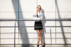 Happy beautiful blonde business woman in modern office. Royalty Free Stock Photography