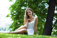Happy beautiful blonde girl calling by phone in a summer park. Happy beautiful girl calling by phone in a summer park Stock Photos