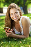 Happy beautiful blonde girl calling by phone in a summer park. Happy beautiful girl calling by phone in a summer park Stock Image