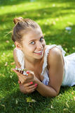 Happy beautiful blonde girl calling by phone in a summer park. Happy beautiful girl calling by phone in a summer park Stock Photo