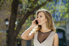 Happy beautiful blonde girl calling by phone in a summer street. Happy beautiful girl calling by phone in a summer street Royalty Free Stock Images