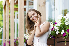 Happy beautiful blonde girl calling by phone in a summer street. Happy beautiful girl calling by phone in a summer street Royalty Free Stock Photography