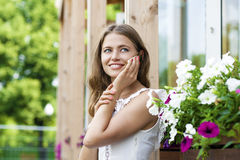 Happy beautiful blonde girl calling by phone in a summer street Royalty Free Stock Images