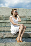 Happy beautiful blonde girl calling by phone in a summer street Royalty Free Stock Photography