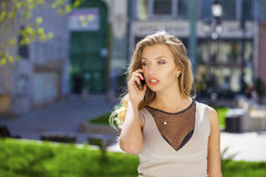 Happy beautiful blonde girl calling by phone in a summer street. Happy beautiful girl calling by phone in a summer street Stock Photos