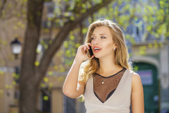 Happy beautiful blonde girl calling by phone in a summer street Stock Photos