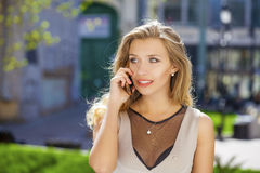 Happy beautiful blonde girl calling by phone in a summer street. Happy beautiful girl calling by phone in a summer street Royalty Free Stock Photos
