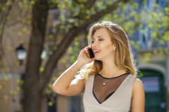 Happy beautiful blonde girl calling by phone in a summer street. Happy beautiful girl calling by phone in a summer street Stock Image