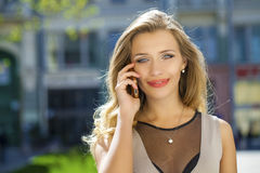 Happy beautiful blonde girl calling by phone in a summer street. Happy beautiful girl calling by phone in a summer street Royalty Free Stock Photo