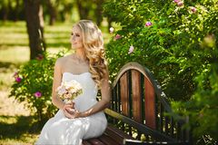 Happy and beautiful blonde model girl with gentle makeup and with wedding hairstyle, in the long white dress sits on a stock images