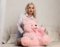 Happy beautiful blonde woman hugging a teddy bear. Concept of holiday or birthday Stock Photos