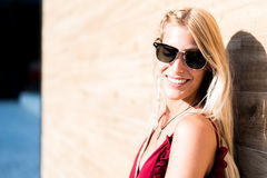 Happy beautiful blonde woman wearing sunglasses smiling in a woo. D wall Royalty Free Stock Image