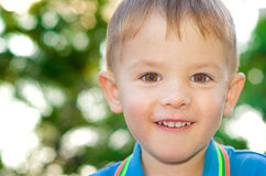 Happy beautiful boy. Portrait of a happy beautiful boy on the background bokeh Royalty Free Stock Photos
