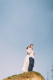 Happy beautiful bride embracing back her groom at top of hill against to the sky Royalty Free Stock Photo
