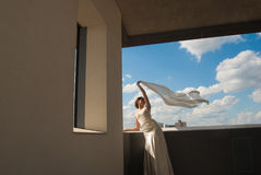 Happy beautiful bride with flying fabric over sky Royalty Free Stock Images