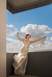 Happy beautiful bride with flying fabric over sky Stock Photos