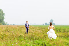 Happy beautiful bride and groom walking on field Stock Photography