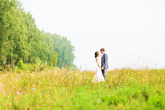 Happy beautiful bride and groom walking on field Stock Photo