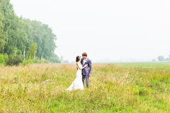 Happy beautiful bride and groom walking on field Royalty Free Stock Photo