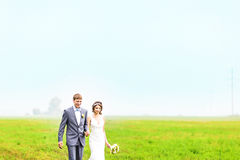 Happy beautiful bride and groom walking on field Royalty Free Stock Photos