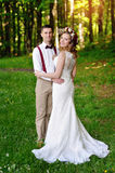Happy beautiful bride and groom walking on field in sunlight Stock Image