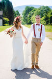 Happy beautiful bride and groom walking on field in sunlight Stock Images