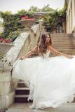 Happy beautiful bride running in blowing wedding dress. Fashion Stock Photo
