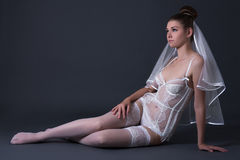 Happy beautiful bride in sexy lingerie sitting over grey Stock Image