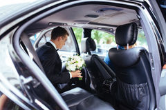 Happy beautiful bride, sitting in wedding car with a bouquet Royalty Free Stock Photos