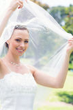 Happy beautiful bride unveiling self in garden Royalty Free Stock Images