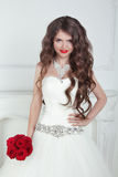 Happy beautiful brunette bride with long wavy hair styling holdi. Ng red roses bouquet Stock Photography