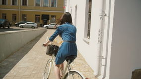 Happy beautiful brunette girl riding a bike in the street turning corner in summertime, slow mo, steadicam shot. Happy beautiful brunette girl on vacation riding stock footage