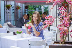 Happy Beautiful brunette girl sitting in a coffee shop Royalty Free Stock Image