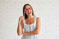 Happy beautiful brunette holding red glasses-mask in the shape o. Happy smiling woman wear white singlet with overalls and holding red glasses-mask in the shape Stock Image
