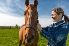 Happy beautiful brunette taking care of her brown horse Stock Photos