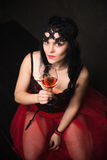 Happy Beautiful brunette woman in corset and long hair with glass of red wine stock photography
