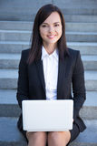Happy beautiful business woman sitting on stairs with laptop Stock Photo
