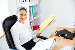 Happy beautiful businesswoman holding binders while sitting at the office Royalty Free Stock Photography