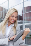 Happy beautiful businesswoman using digital tablet against office building Stock Photo