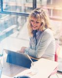 Happy beautiful businesswoman working at the modern office loft.Coworker using electronic touch tablet computer on sunny. Workplace.Vertical. Blurred background royalty free stock image