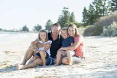 Happy beautiful Caucasian family having holidays on the beach smiling with mother and father sitting on sand with little son and y Royalty Free Stock Photos