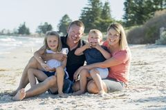 Happy beautiful Caucasian family having holidays on the beach smiling with mother and father sitting on sand with little son and y Stock Photos