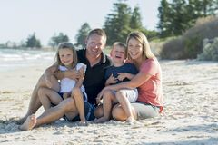 Happy beautiful Caucasian family having holidays on the beach smiling with mother and father sitting on sand with little son and y Stock Image