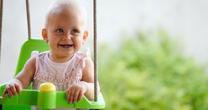 Happy cheerful baby smiling while on swing stock photography