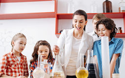 Happy beautiful chemistry teacher conducting an experiment Royalty Free Stock Image