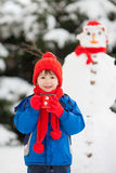 Happy beautiful child building snowman in garden, winter time, h Stock Image