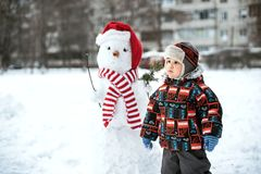 Happy beautiful child building snowman in garden, winter time, royalty free stock images